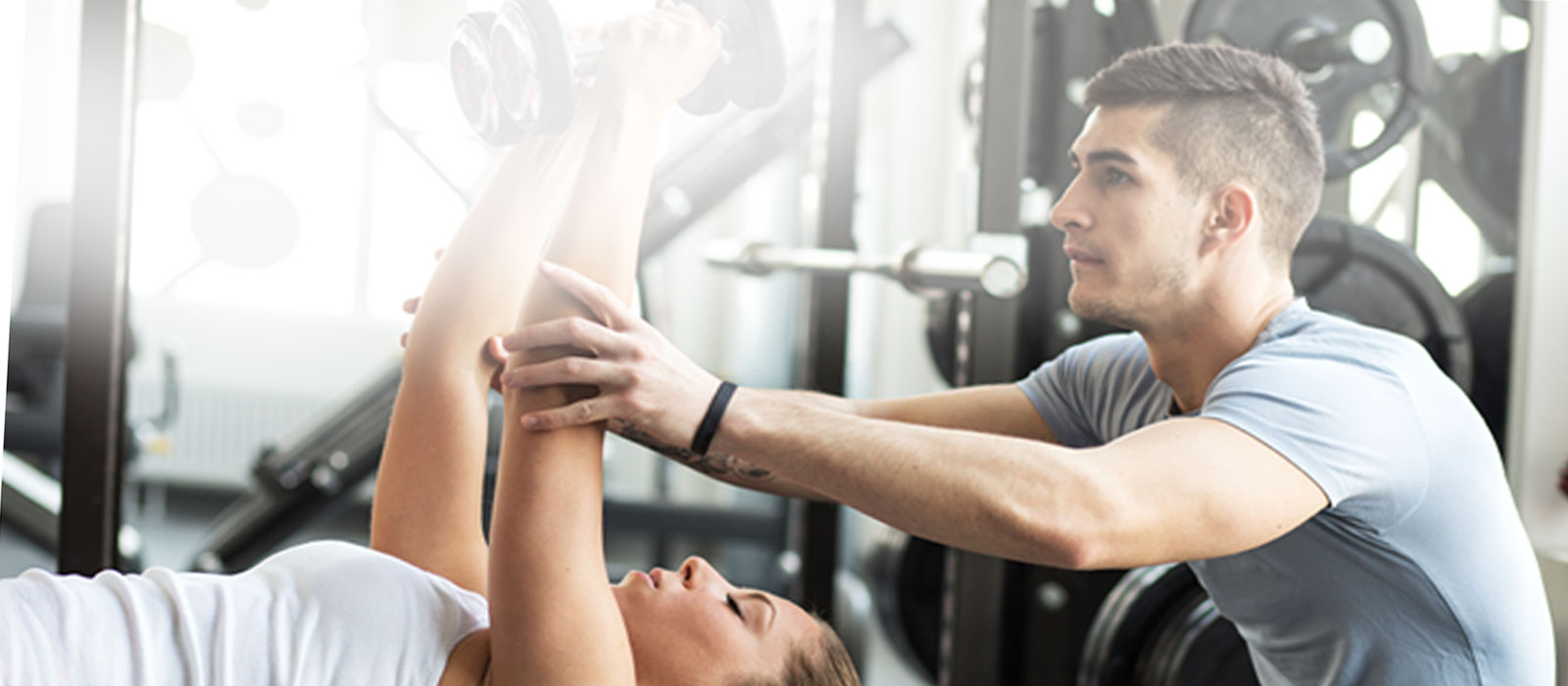 personal trainer in Cincinnati assisting gym member with proper body mechanics during workout