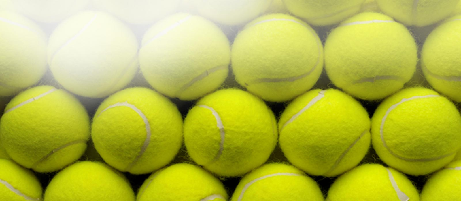 rows-of-yellow-tennis-balls-stacked-up